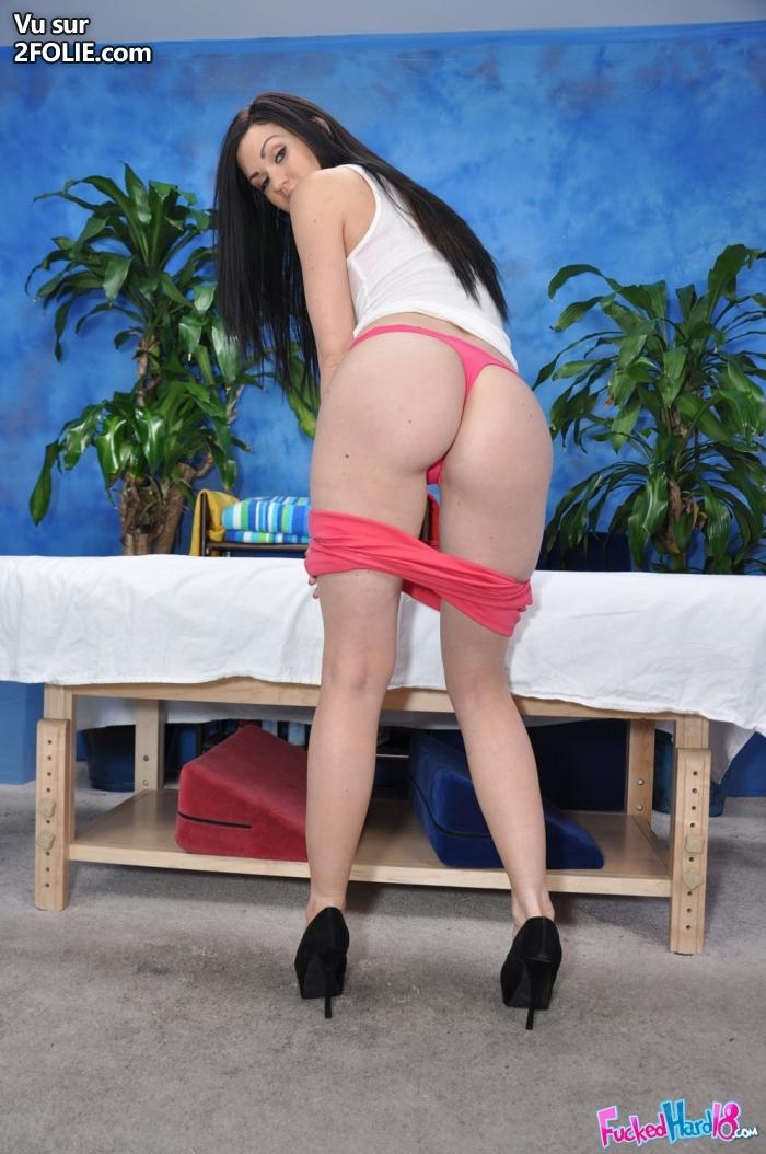 une belle femme retire son soutien-gorge noir et rouge pour montrer sa splendide paire de poitrine